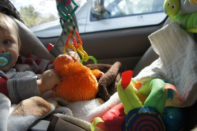 O in car seat with toys